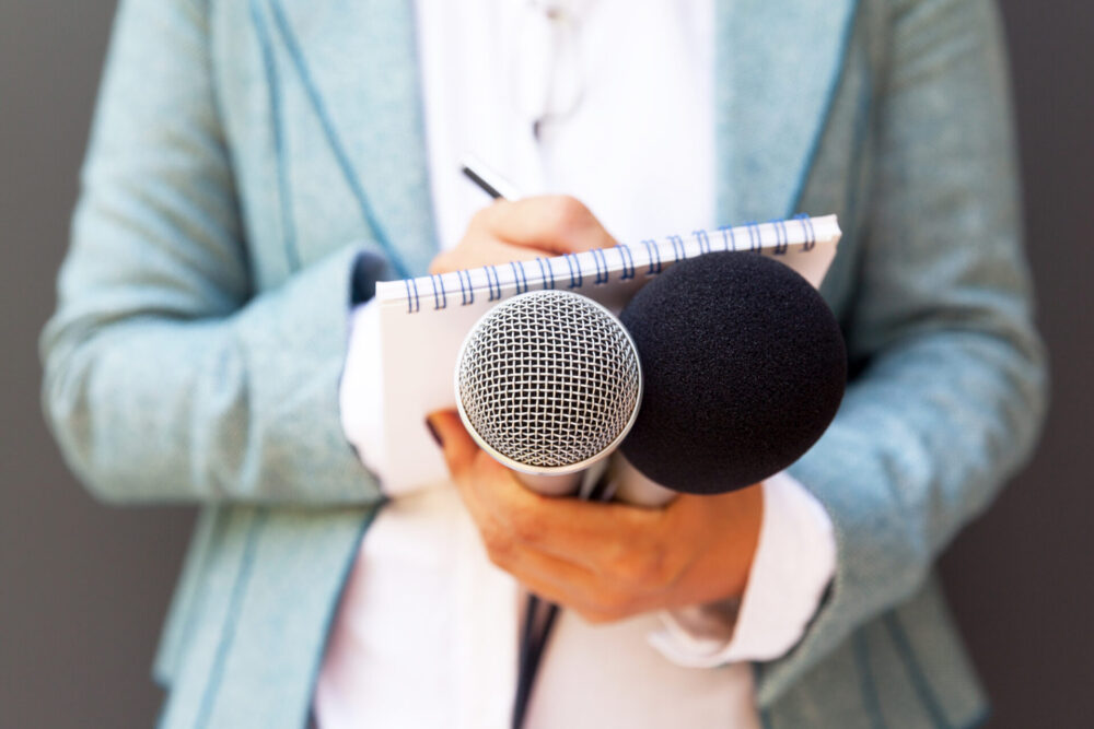 Female,Reporter,At,Press,Conference,,Writing,Notes,,Holding,Microphone